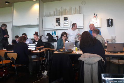 Zdjęcie z warsztatów, dwie grupki osób rozmawiają ze sobą