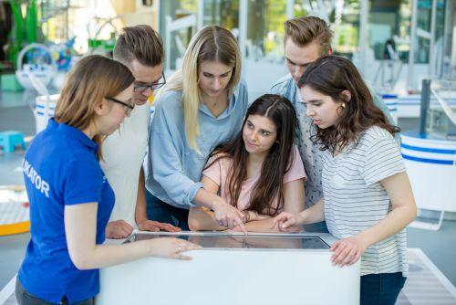 Grupa osób w różnym wieku z zainteresowaniem słucha edukatorki opisującej działanie stanowiska.