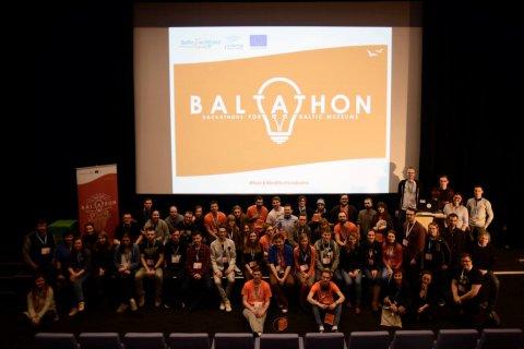 Kilkadziesiąt osób pozuje do wspólnego zdjęcia na scenie. W tle slajd z napisem Baltathon