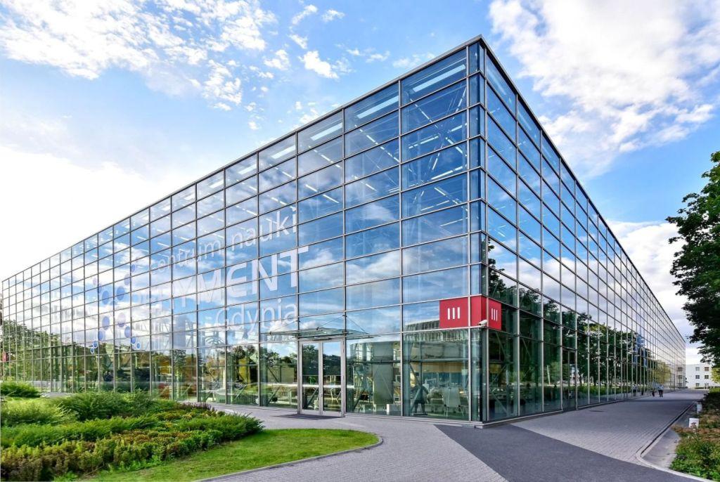 Narożnik budynku Centrum Nauki Experyment. W całkowicie przeszklonych ścianach odbijają się trawniki oraz błękitne niebo i chmury.