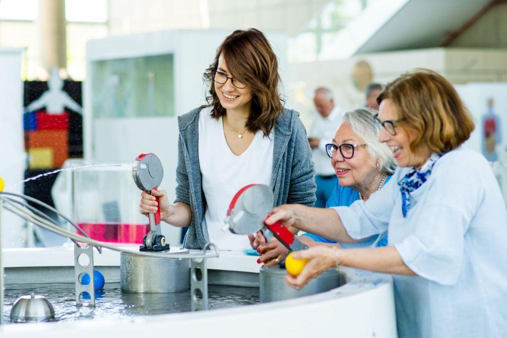 Trzy uśmiechnięte kobiety, młoda, w średnim wieku oraz starsza, przy pomocy wodnych pistoletów przemieszczają po torach plastikowe piłki.