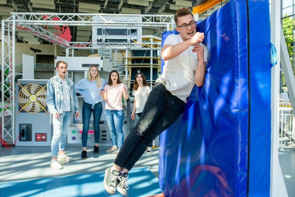 Młody mężczyzna podskakuje uderzając ramieniem o pionowo stojący materac. Mierzy w ten sposób swoją siłę uderzenia.