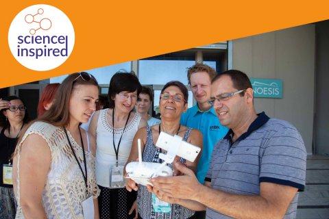 Grupa osób spogląda na przenośne urządzenie elektroniczne, w rogu zdjęcia logo Science Inspired