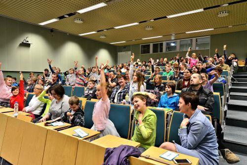 Kilkudziesięcioro dzieci siedzi w sali wykładowej, większość z nich podnosi rękę do góry, zgłaszając się