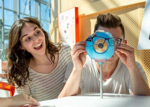 Młoda dziewczyna uśmiecha się do chłopaka przykładającego okulary do modelu oka