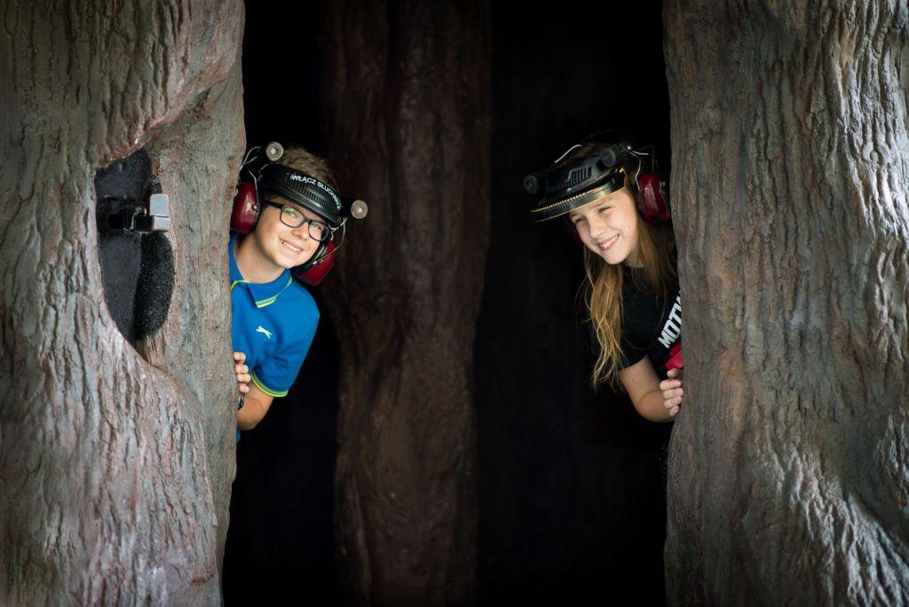 Dwoje dzieci wychyla się z wnętrza pnia sztucznego drzewa. Na głowach mają słuchawki pozwalające poznać zjawisko echolokacji.