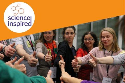 Grupa osób stoi w kółku, pokazując znak ok, w rogu zdjęcia logo Science Inspired