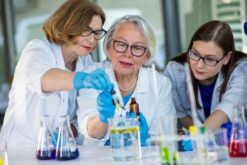 Edukatorka tłumaczy dwóm kobietom reakcje chemiczne