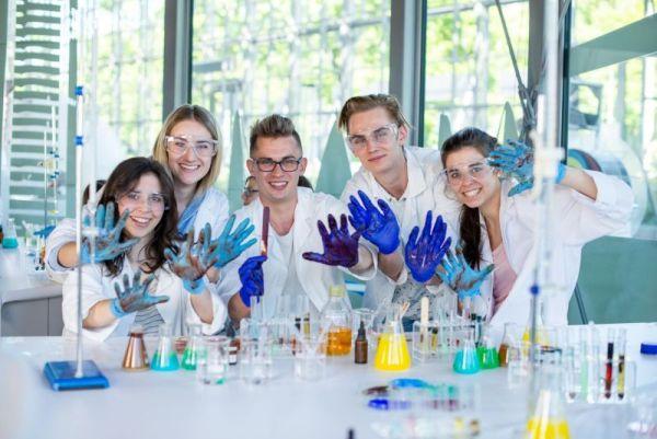 Trzy dziewczyny i dwóch chłopaków pozuje do zdjęcia w niebieskich rękawiczkach, wszyscy się uśmiechają. Przed nimi na stole leżą liczne odczynniki chemiczne i szkło laboratoryjne
