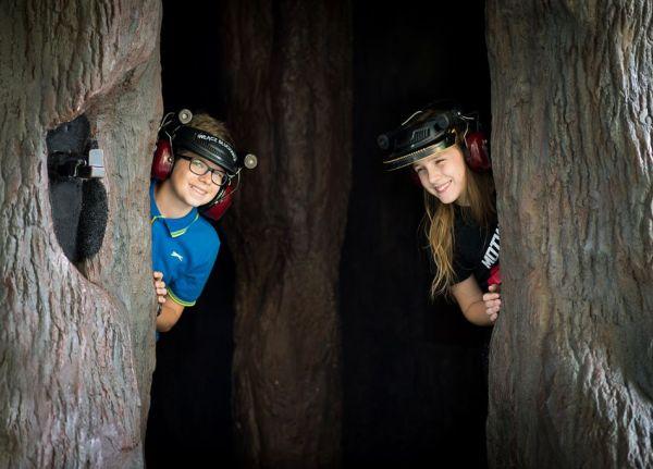 Dwoje dzieci stoi wewnątrz drzewa. Na głowach mają słuchawki pozwalające poznać zjawisko echolokacji.