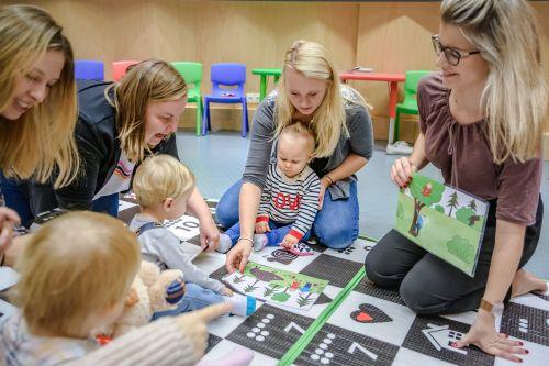 Cztery kobiety bawią się dziećmi na macie sensorycznej