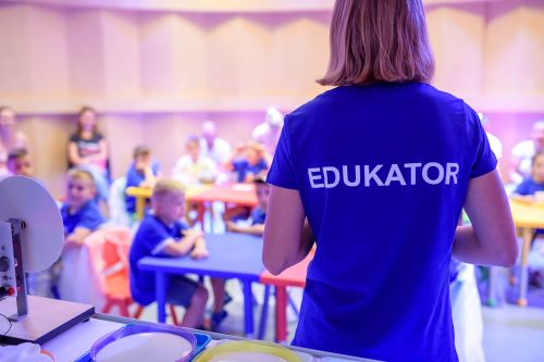 Osoba w niebieskiej koszulce, z napisem edukator na plecach. W tle grupa dzieci, siedząca przy kolorowych stolikach