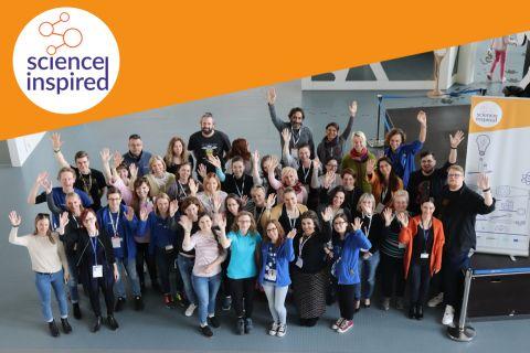 Grupa osób pozuje i macha do zdjęcia, w rogu zdjęcia logo Science Inspired