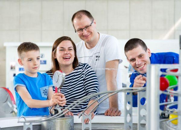 Chłopiec w niebieskiej koszulce w towarzystwie dwóch dorosłych osób i edukatora w niebieskim polarze celuje z pistoletu wodnego