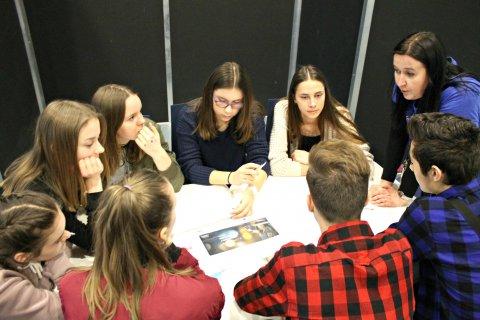 Dziewięć osób pracujących w grupie, przy jednym stole