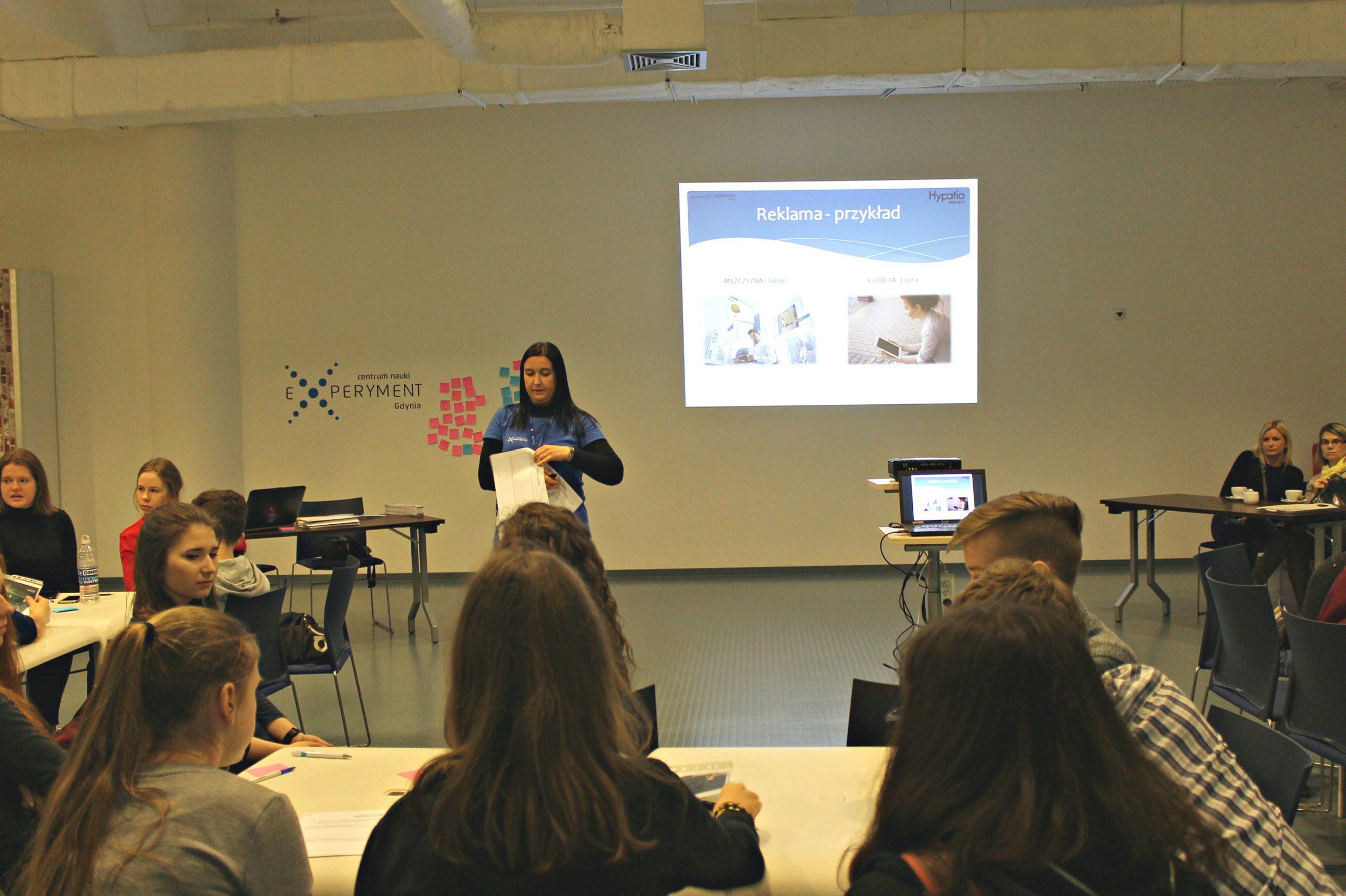 Kobieta prowadzi wykład przed grupą młodzieży
