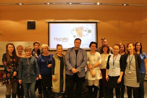 Grupa kobiet i mężczyzn pozuje do zdjęcia, w tle slajd z napisem Hypatia