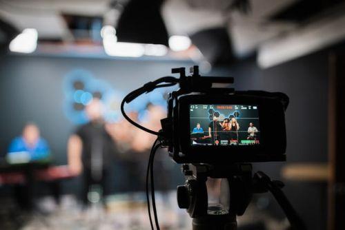 Na pierwszym planie wyświetlacz aparatu cyfrowego nagrywającego piątkę osób