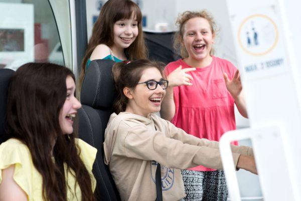 Cztery dziewczęta z uśmiechami na twarzach korzystają ze stanowiska na wystawie Kierunek Zdrowie