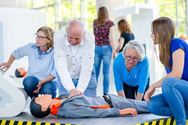 Mężczyzna uczy się pierwszej pomocy na fantomie, obok niego dwie kobiety oraz edukatorka