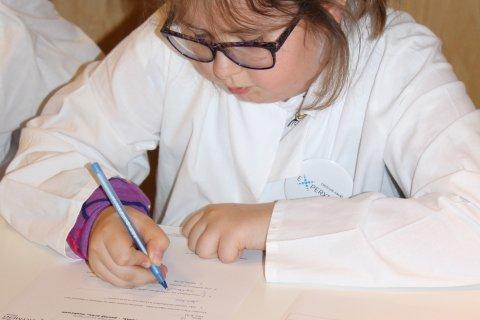 Dziewczynka w okularach zapisująca coś na kartce