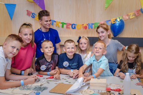 Grupka dzieci pozuje do zdjęcia, za nimi ubrany na niebiesko edukator