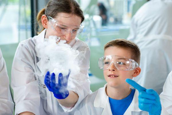 Kobieta w okularach ochronnych prezentuje doświadczenie chemiczne chłopcu w okularach ochronnych