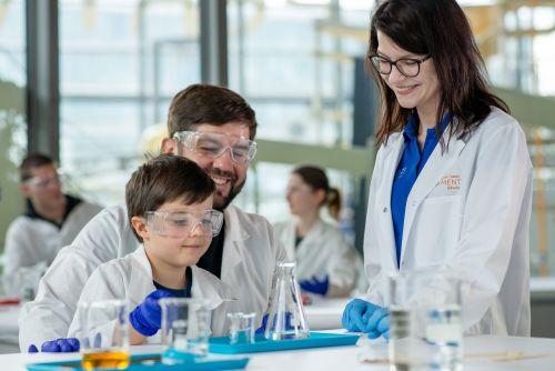 Uśmiechnięta kobieta tłumaczy eksperymenty chemiczne mężczyźnie z dzieckiem. którzy siedzą przy stole. Przed nimi szkło laboratoryjne