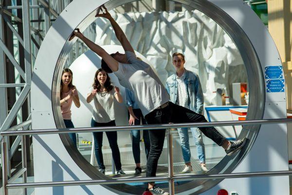 Młody mężczyzna korzystający z kołowrotka w Experymencie i trójka młodych ludzi dopingujących go