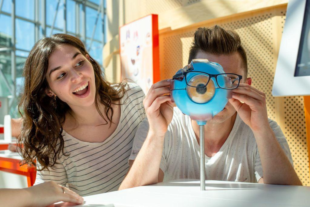Młody mężczyzna wkłada swoje okulary na model dużej gałki ocznej.