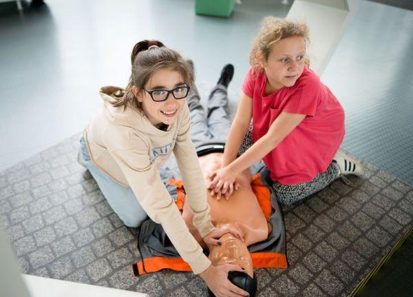 Nastolatki ćwiczą resuscytację krążeniowo-oddechową na manekinie.