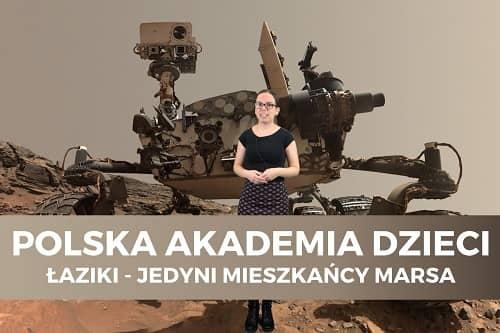 Miniaturka filmu z cyklu Polska Akademia Dzieci pt. Łaziki - jedyni mieszkańcy Marsa. Na zdjęciu kobieta na tle łazika marsjańskiego.