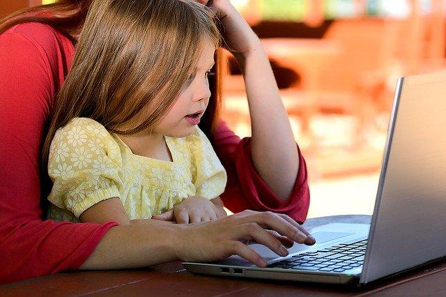 Dziecko na kolanach mamy korzysta z komputera