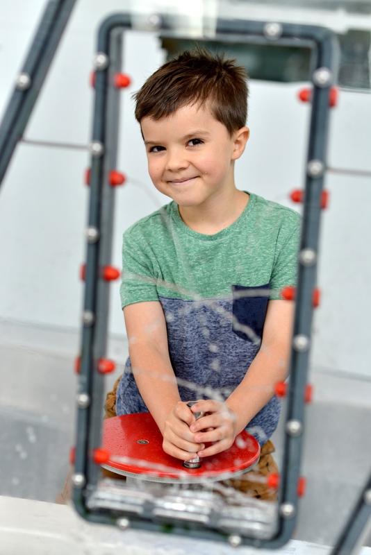 Na zdjęciu jest chłopiec w wieku około 7 lat na wystawie hydroświat w Centrum Nauki EXPERYMENT