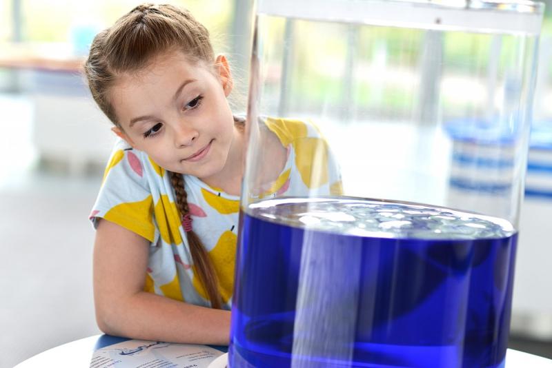 Na zdjęciu jest dziewczynka na wystawie hydroświat w Centrum Nauki EXPERYMENT