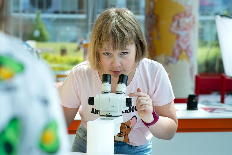 Na zdjęciu jest dziewczynka w wieku około 12 lat przy mikroskopie na wystawie w Centrum Nauki EXPERYMENT