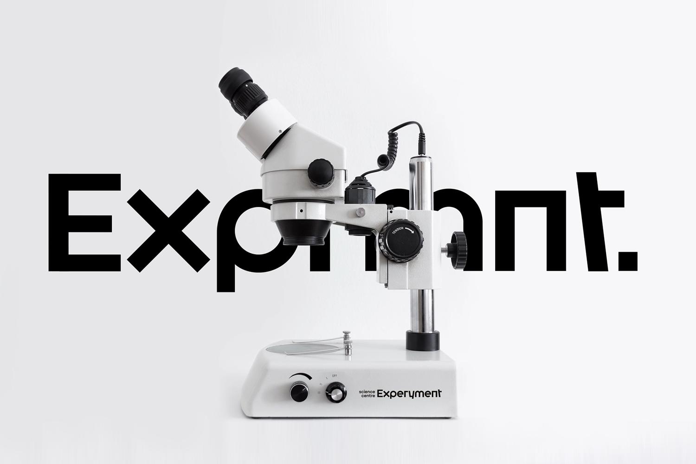 Na zdjęciu widać mikroskop z nowym logotypem Experymentu w tle