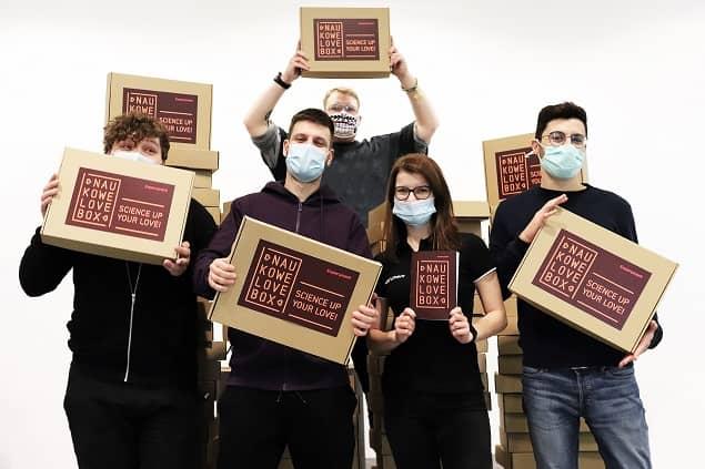 Grupa osób w maseczkach stoi obok siebie, w rękach mają kartony z napisem NaukoweLove BOX.
