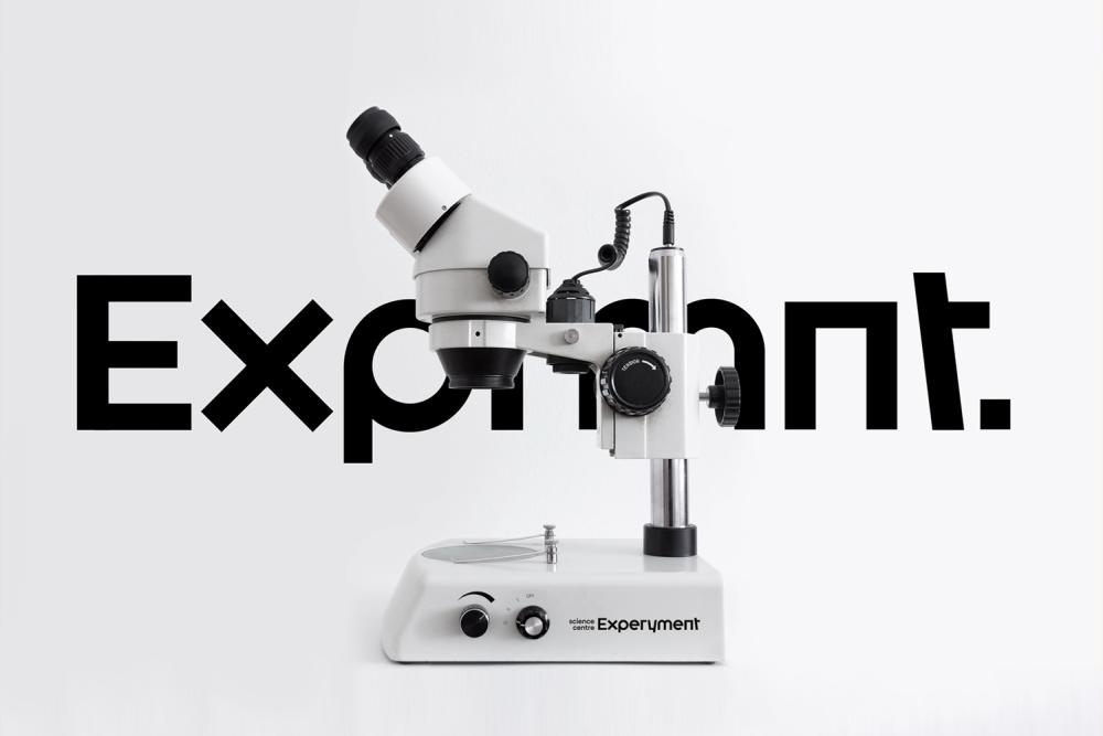 Na zdjęciu widać mikroskop na tle jednego z wariantów nowego logo Centrum Nauki Experyment.