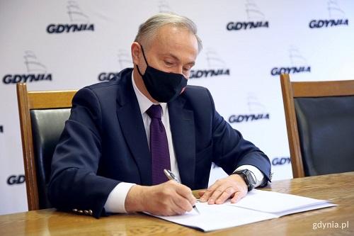 Prezydent Wojciech Szczurek podpisuje dokumenty.