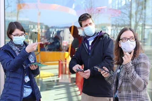 Trzy osoby w maseczkach z telefonami w dłoniach.