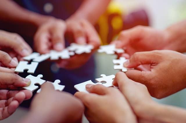Zdjęcie kilku osób, które trzymają puzzle.