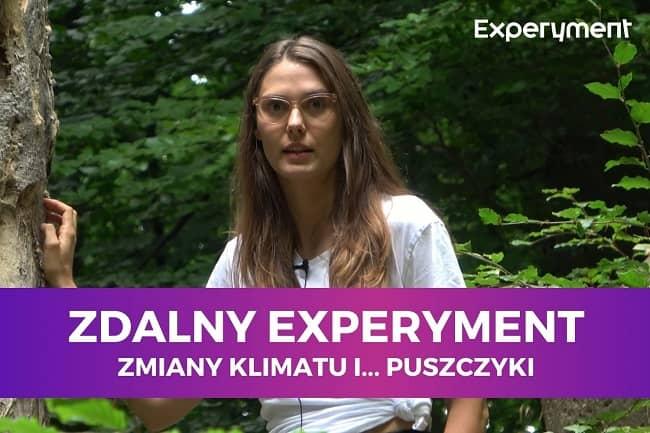 Miniaturka do filmu z cyklu ZDALNY EXPERYMENT pod tytułem Zmiany klimatu i puszczyki. Na zdjęciu kobieta w okularach stojąca obok drzewa